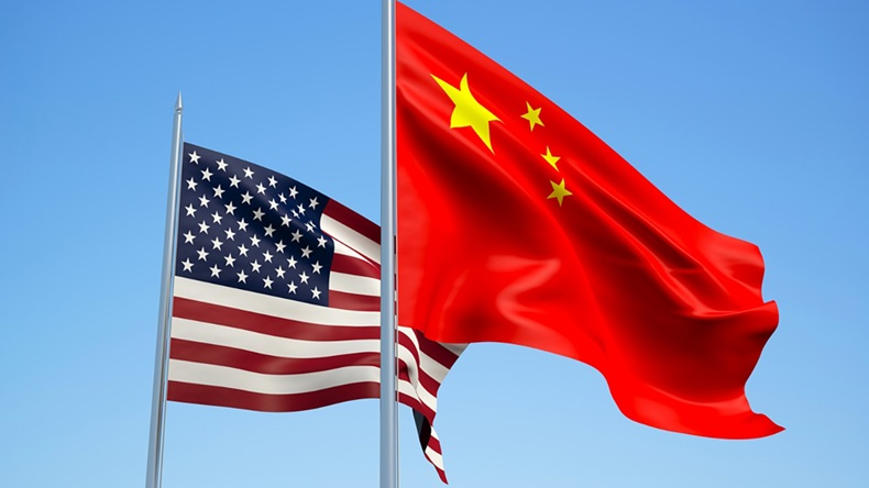 Flags of China and USA fly against blue sky