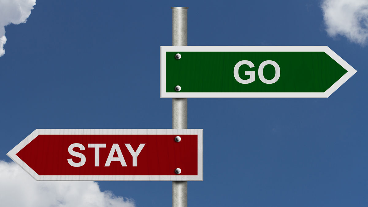 Red and green street signs with blue sky with words Stay and Go, Stay versus Go