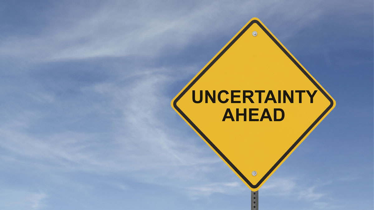 """Uncertainty Ahead"" sign on a background of blue sky with clouds"
