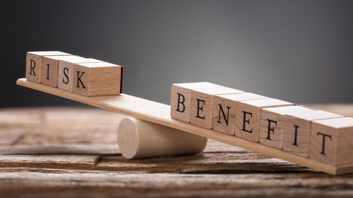 Closeup of risk and benefit wooden blocks on seesaw against gray background - Image