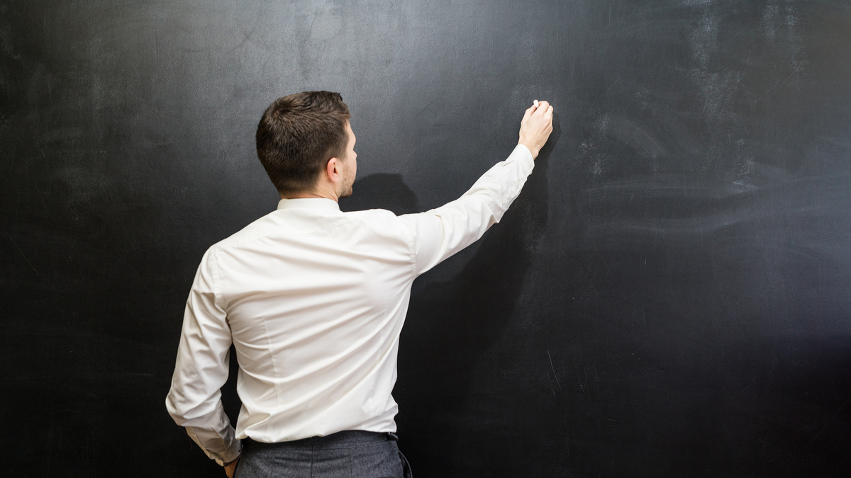 Man in suit pointing something on chalkboard,back view,isolated.Copyspace blank.Teacher writing on black board - Image
