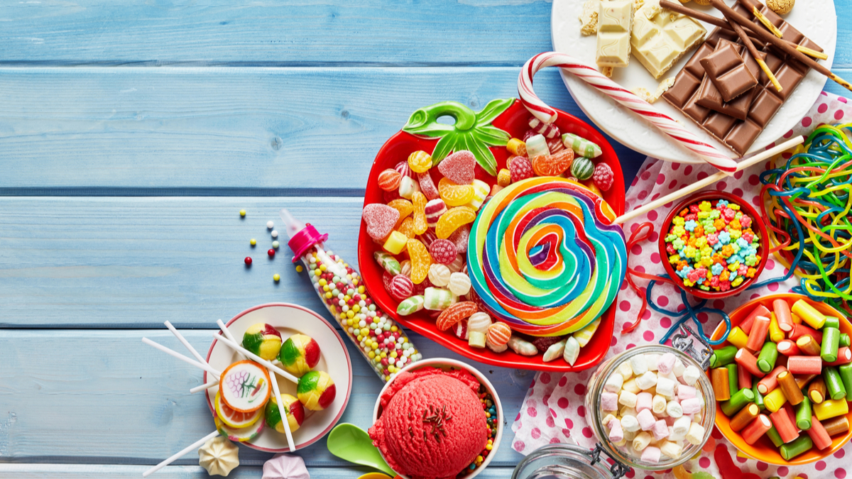 Overhead view of colorful array of different childs sweets and treats in bowls on light blue wood background - Image