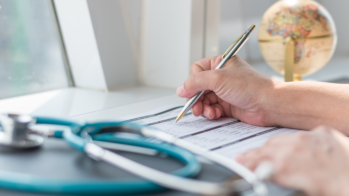 Physician doctor writing on medical health care record, patients discharge, or prescription form paperwork in hospital clinic - Image