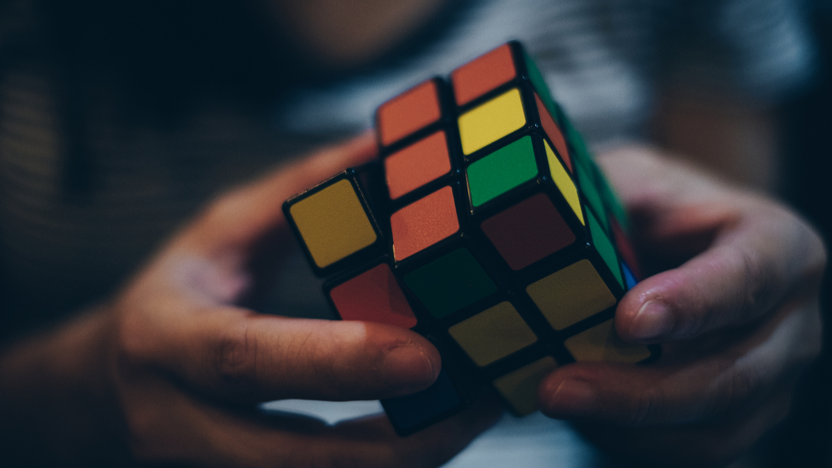 KORONADAL CITY, PHILIPPINES – JANUARY 28, 2017: Rubik's Cube was invented in 1974 by Hungarian sculptor and professor of architecture Erno Rubik. Hands of a young lady trying to solve the puzzle. - Image