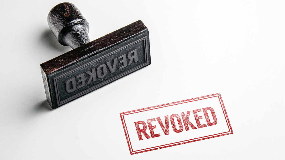 Rubber stamping that says 'Revoked'. - Image