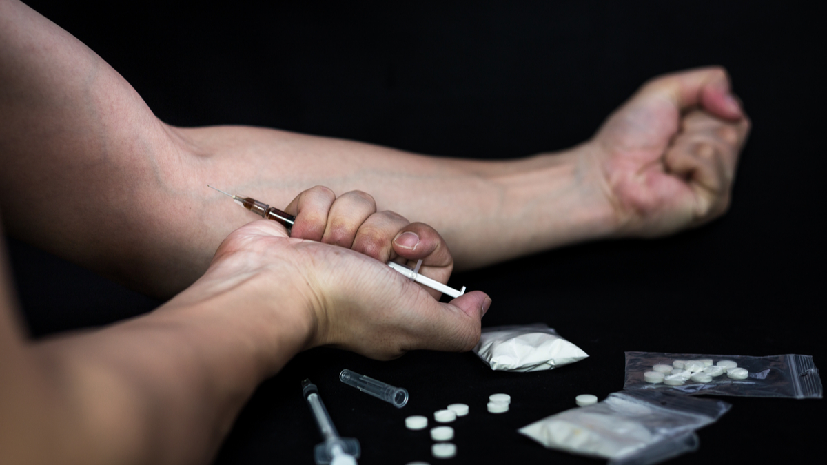 Addict man make injection of drugs