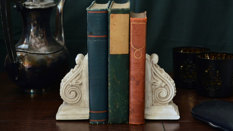 Vintage books enclosed by old fashioned bookends with a moody dark background