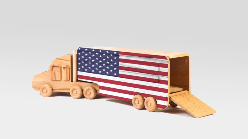 Close-up of a wooden toy truck with a painted national flag USA. The concept of export-import,transportation, national delivery of goods