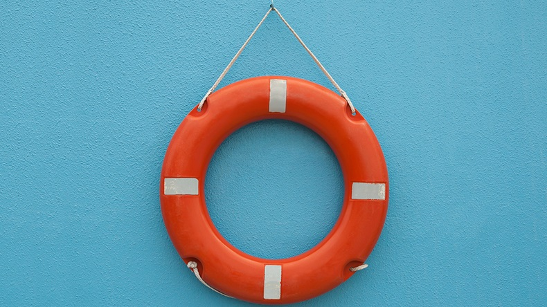 Red life buoy hanging on a blue wall
