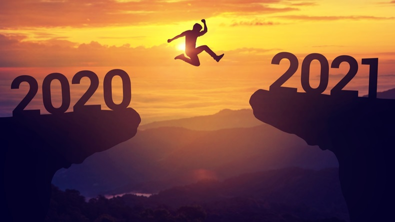 Silhouette man jump between 2020 and 2021 years with sunset background, Success new year concept