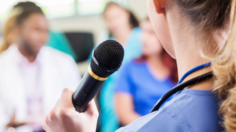 Female healthcare provider addresses colleagues at medical conference