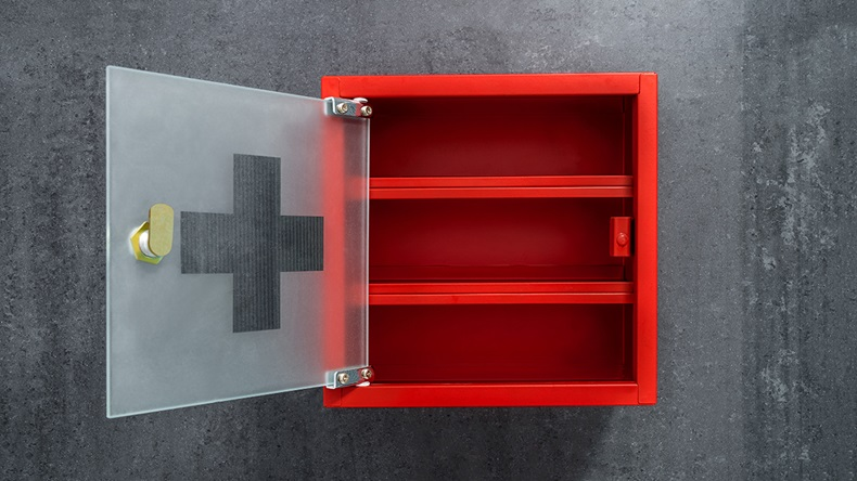 Open red metal empty medicine cabinet hanging on a dark gray marble wall background