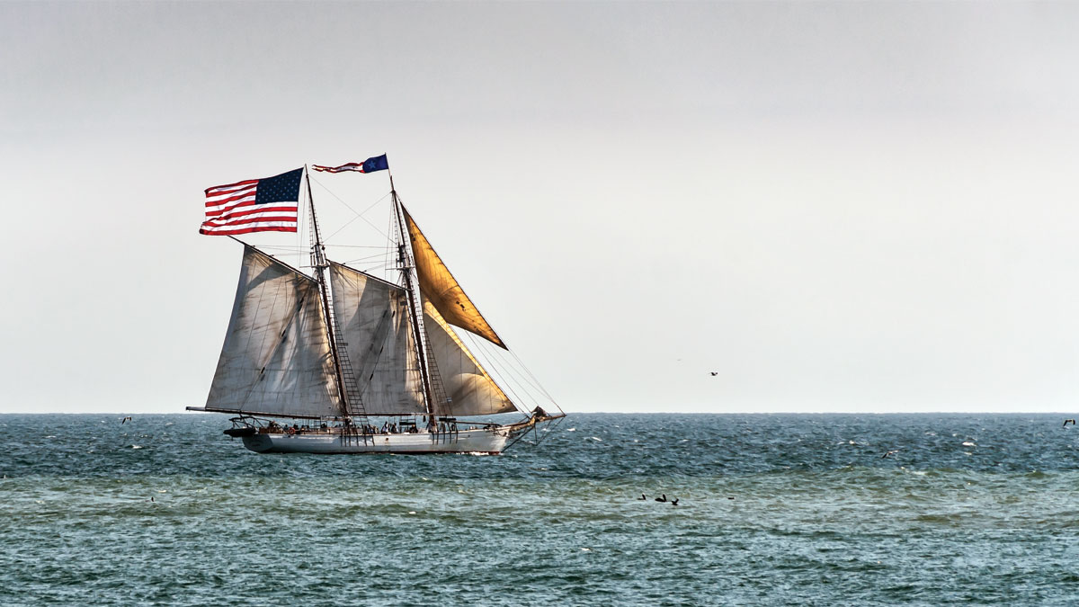 Large US American flag on sailboat off the coast of California