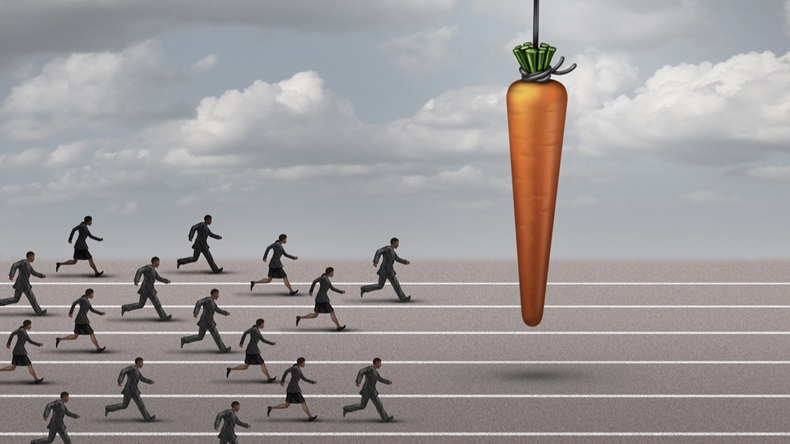 incentive business concept as a group of businessmen and businesswomen run on a track towards a dangling carrot on a moving cable