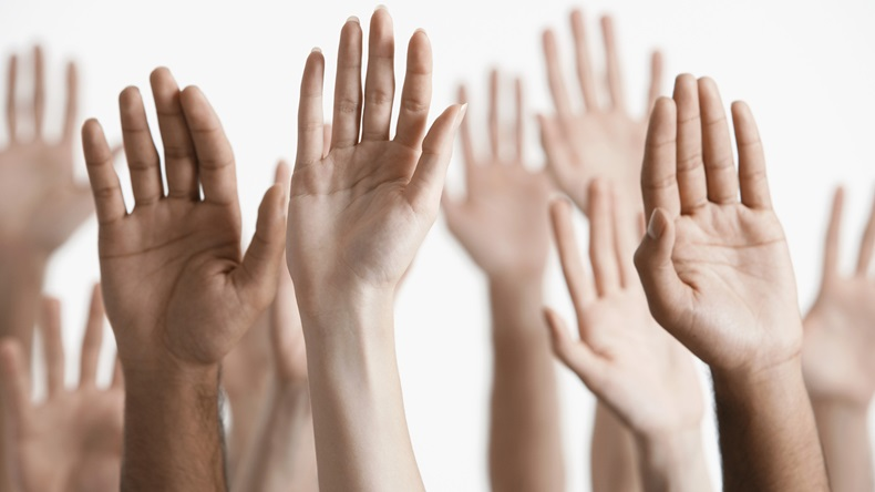 Closeup of multiethnic men and women raising hands against white background. Shutterstock-144918361