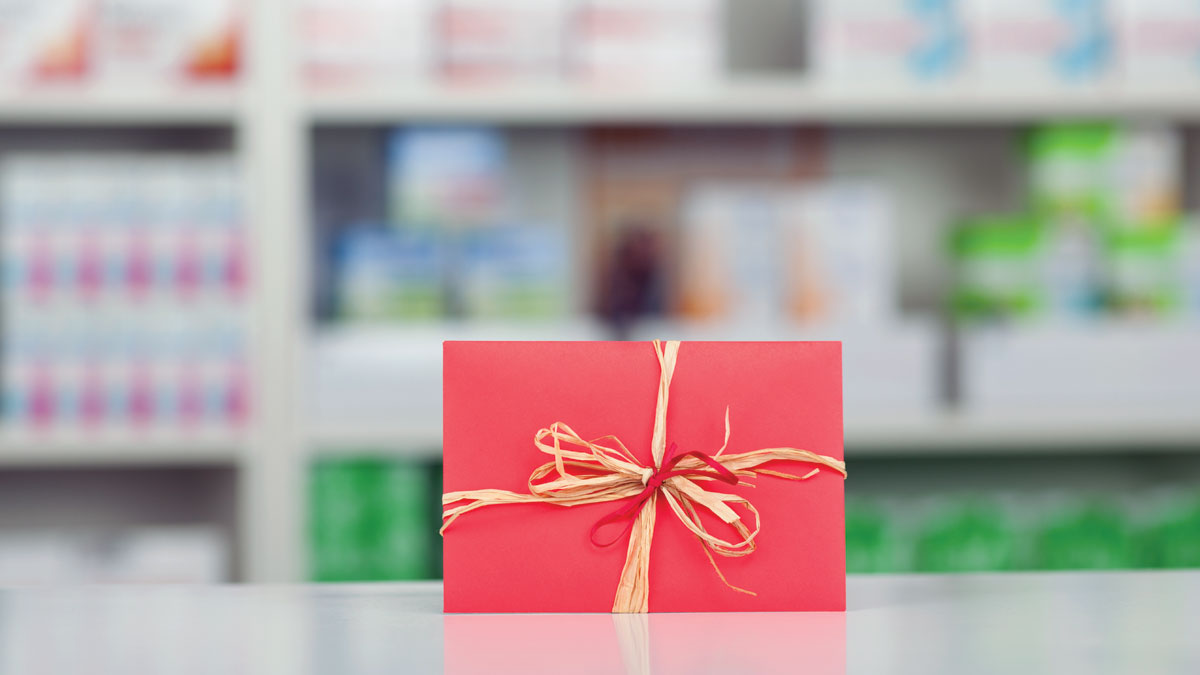 Closeup of gift wrapped in red paper and bow at pharmacy counter