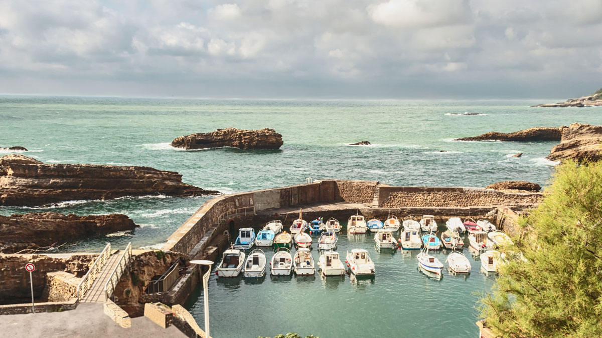 boats are safely tucked for a stone wall from the waves of the ocean/boats in a quiet Harbor on the Atlantic coast of Spain