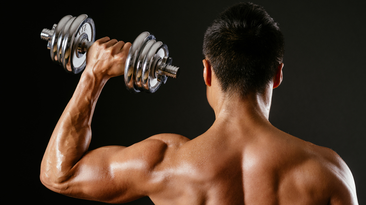 Photo of an Asian male exercising with dumbbells and doing a single shoulder press over dark background.