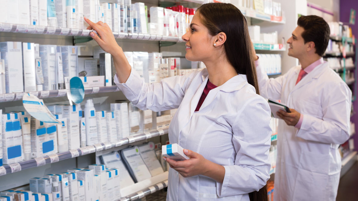 Smiling pharmacist and indian pharmacy technician posing in drugstore