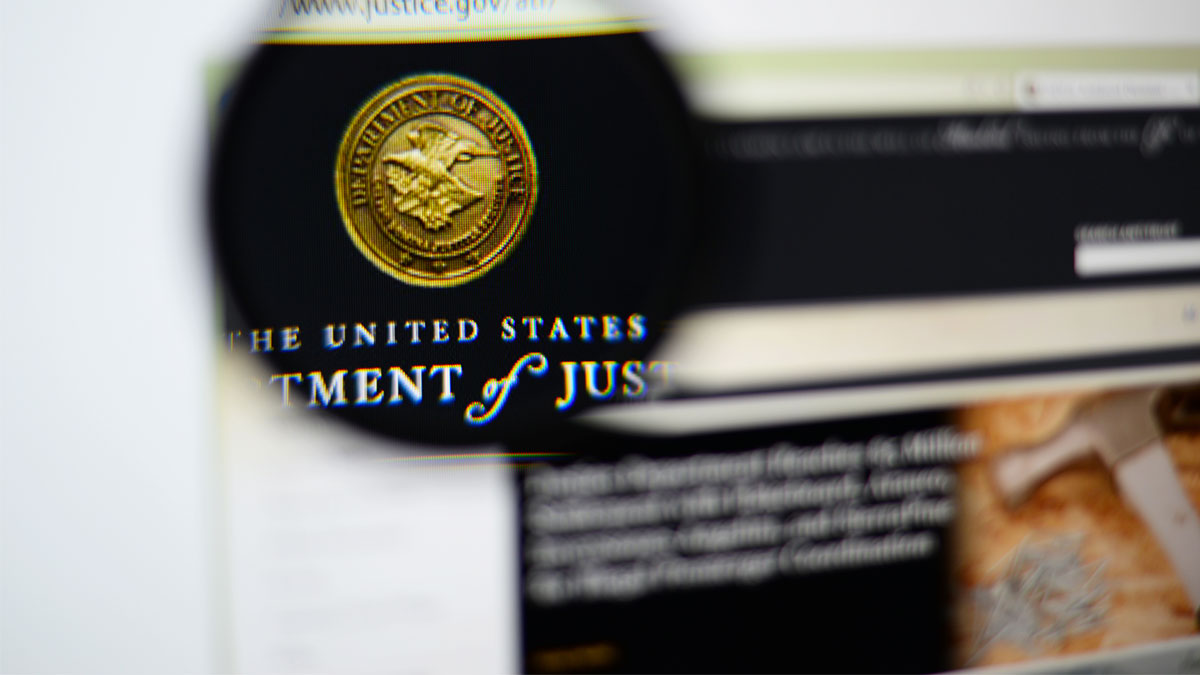 LISBON, PORTUGAL - December 9, 2014: Photo of the United States Department of Justice (DOJ) homepage on a monitor screen through a magnifying glass.
